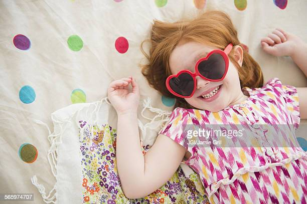 Caucasian girl wearing heart -shaped sunglasses on bed
