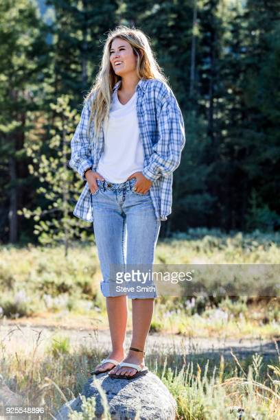 caucasian girl wearing plaid shirt standing on rock - girl wear jeans and flip flops stock photos and pictures