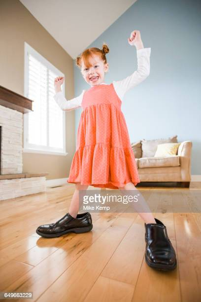 caucasian girl wearing shoes of father in living room - girl shoes stock pictures, royalty-free photos & images