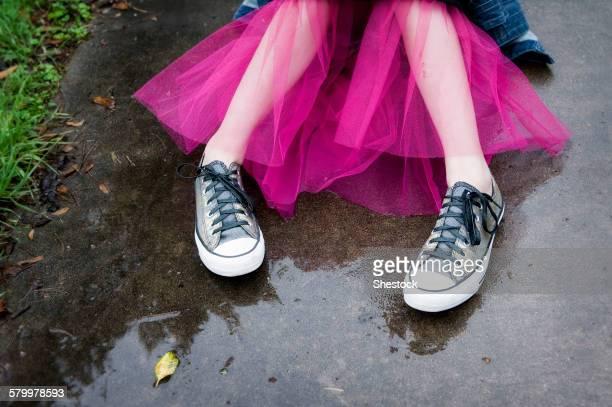 caucasian girl wearing sneakers and tutu in puddle - rok stockfoto's en -beelden
