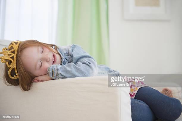 Caucasian girl wearing tiara in armchair