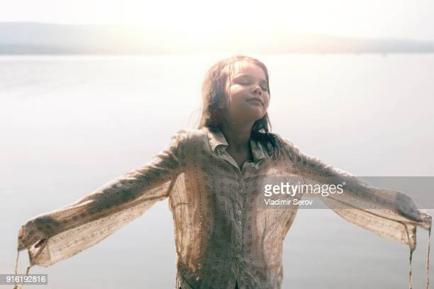 caucasian girl wearing wet shirt near sunny lake - wet shirt stock photos and pictures