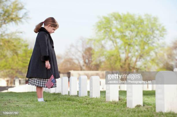 Caucasian girl with American flag visiting cemetery