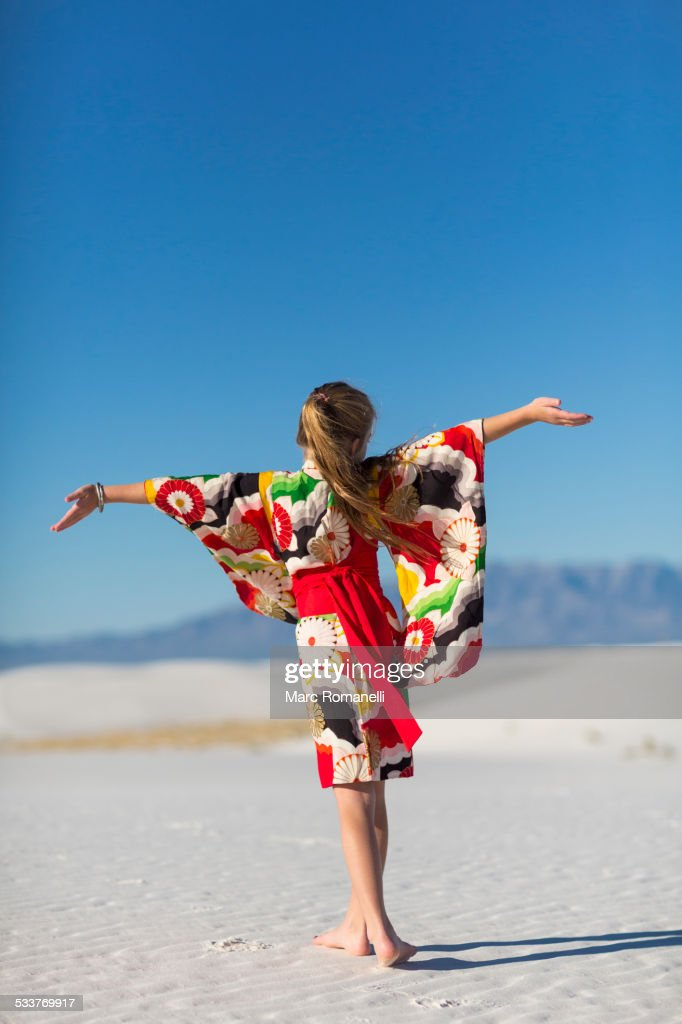Caucasian girl with arms outstretched on sand dune : Foto stock