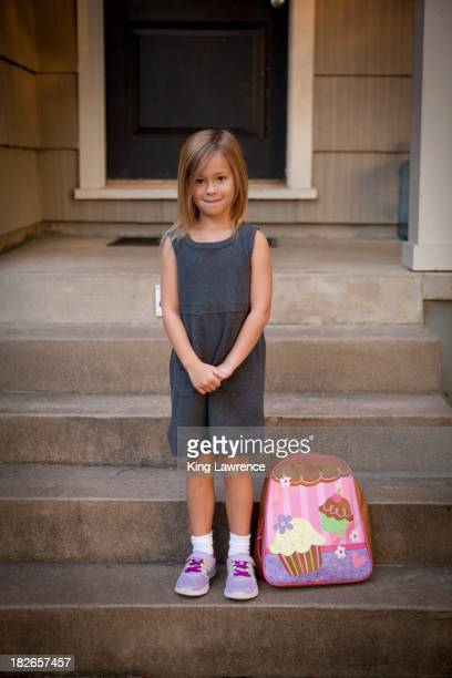 Caucasian girl with backpack on front steps