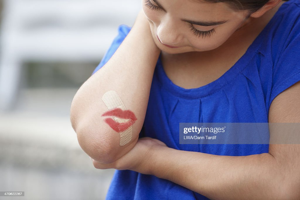 Caucasian girl with lipstick kiss over bandage on elbow : Stock Photo