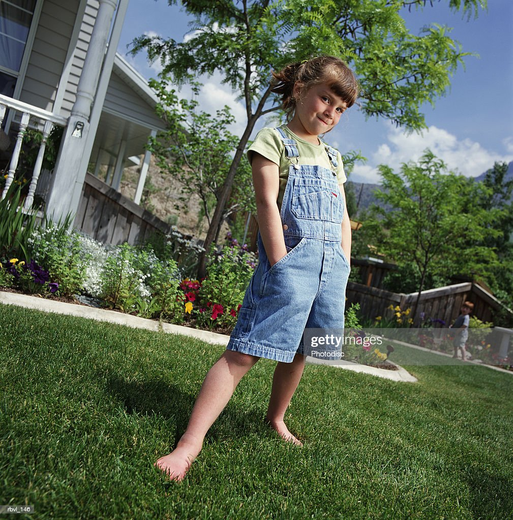 caucasian girl with ponytail wears short overalls hands in pocket stands on lawn bordered by flowers : Foto de stock