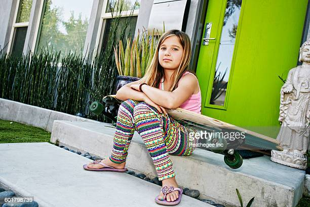 Caucasian girl with skateboard on front stoop