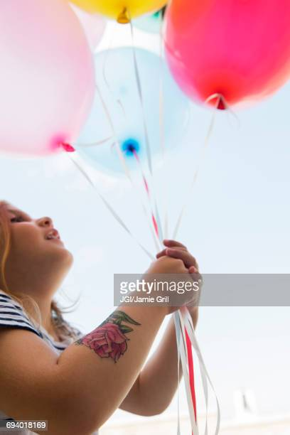 caucasian girl with temporary arm tattoo holding balloons - temporary stock pictures, royalty-free photos & images