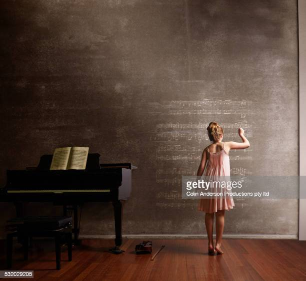 Caucasian girl writing music on blackboard