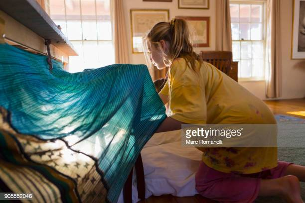 Caucasian girls building fort under table