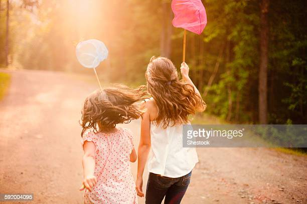 caucasian girls carrying butterfly nets on dirt road - lane sisters stock photos and pictures