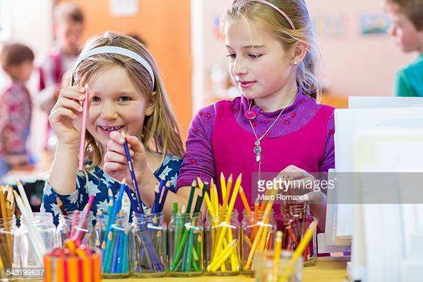 Caucasian girls choosing multicolor pencils in classroom