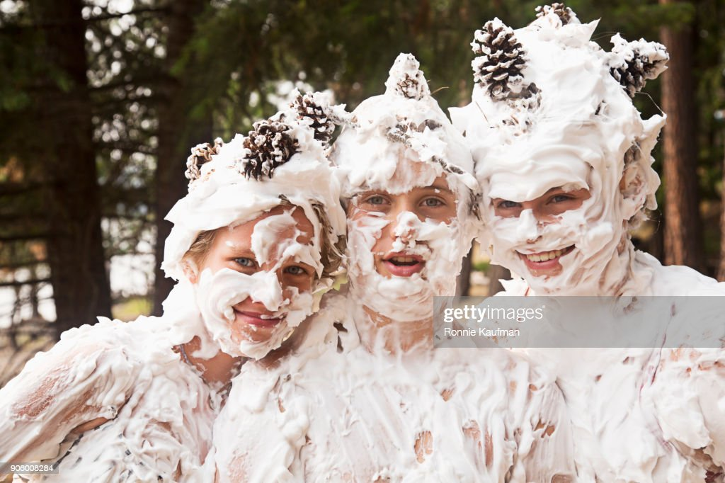 Caucasian girls covered with whipped cream and pine cones : Stock Photo