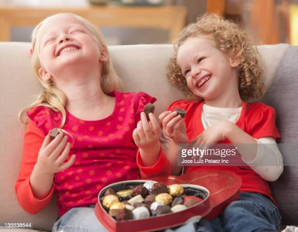 caucasian girls eating valentine's candy - box of chocolate stock pictures, royalty-free photos & images