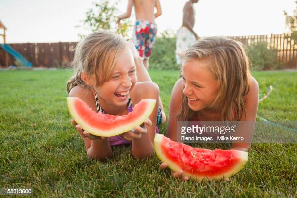 Caucasian girls eating watermelon