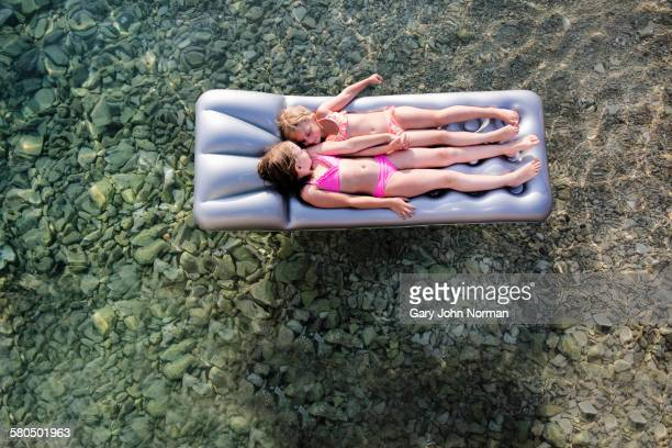 Caucasian girls floating on raft in lake