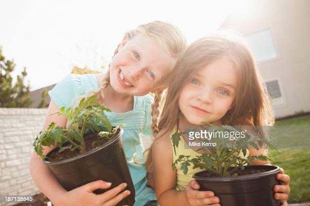 Caucasian girls gardening together