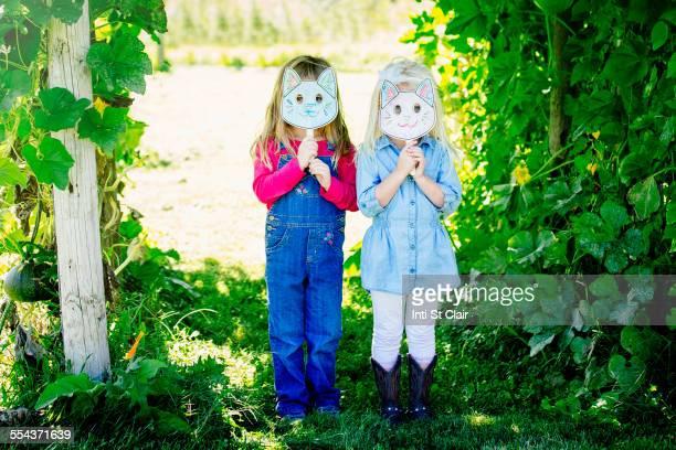 Caucasian girls holding cat mask