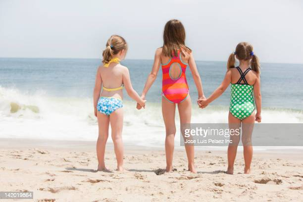 Caucasian girls holding hands on beach