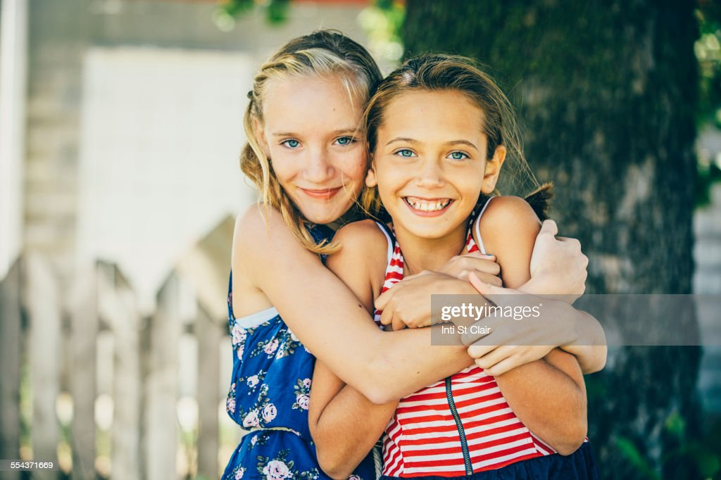 Caucasian girls hugging outdoors : Stock Photo