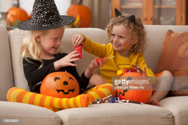 caucasian girls in halloween costumes eating candy - halloween candy stock photos and pictures