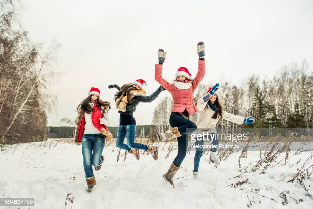 Caucasian girls jumping for joy in snow
