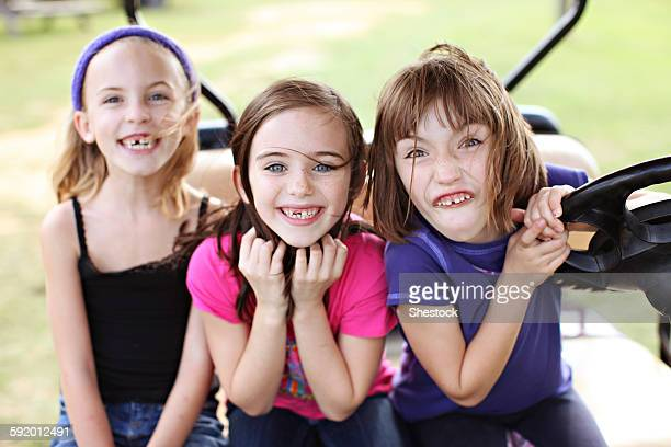 Caucasian girls making faces in golf cart