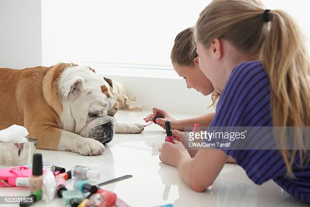 Caucasian girls painting nails of pet dog