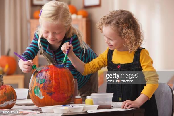 Caucasian girls painting pumpkin