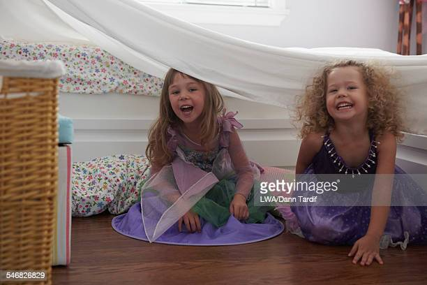 Caucasian girls playing in princess costume in blanket fort