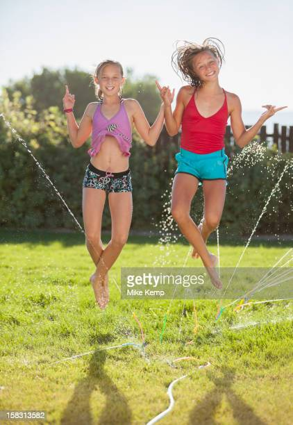 caucasian girls playing in sprinkler - tween girls hot stock photos and pictures