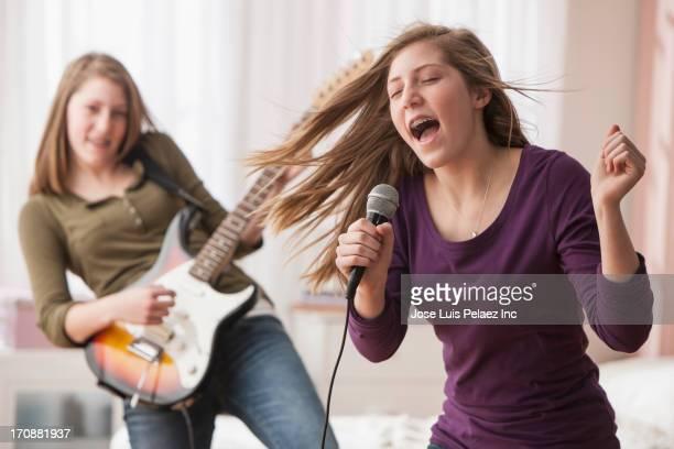 caucasian girls playing music in bedroom - popmuzikant stockfoto's en -beelden