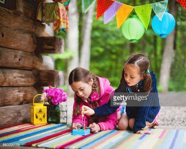 Caucasian girls playing with toy on cabin porch