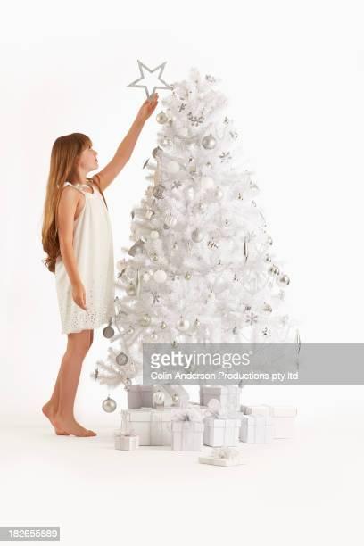 Caucasian girls putting star on Christmas tree