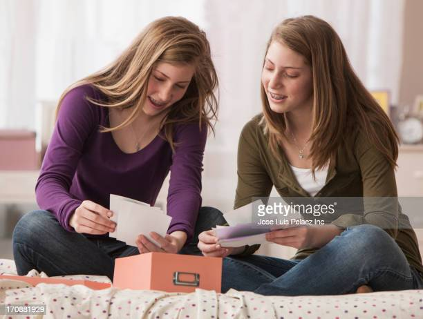 Caucasian girls reading notes on bed