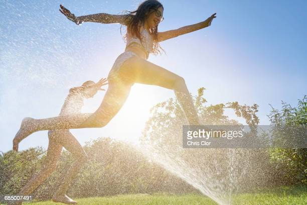 Caucasian girls running and jumping through backyard sprinkler
