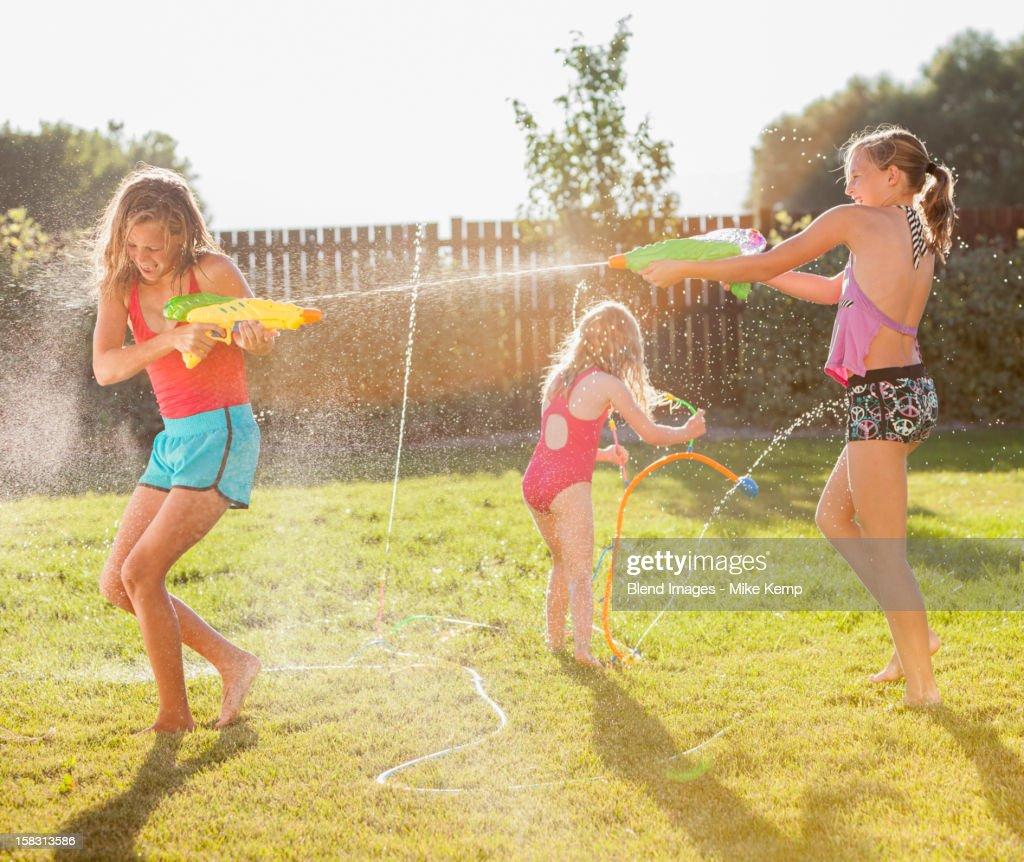 Caucasian girls shooting water guns : Foto de stock