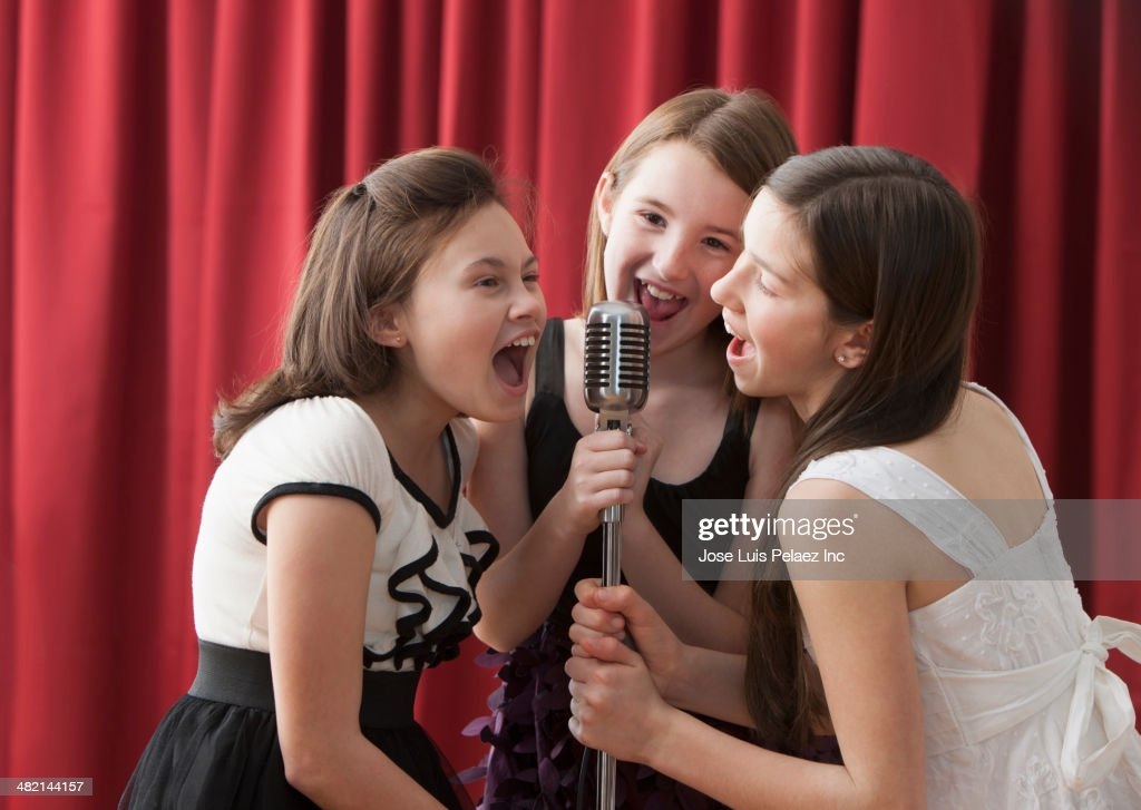 caucasian girls singing into microphone on stage stock