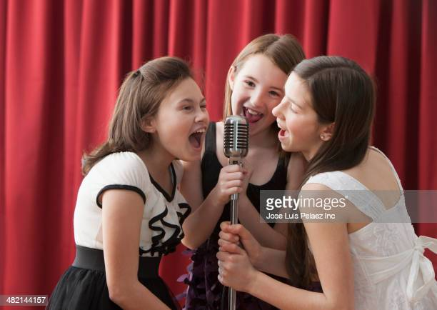 Caucasian girls singing into microphone on stage