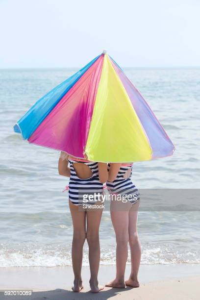 Caucasian girls under umbrella on beach
