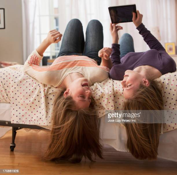 Caucasian girls using digital tablet on bed