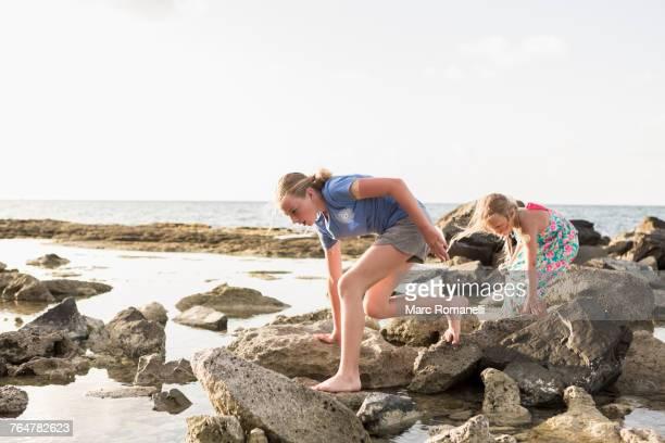 Caucasian girls walking on rocks at beach