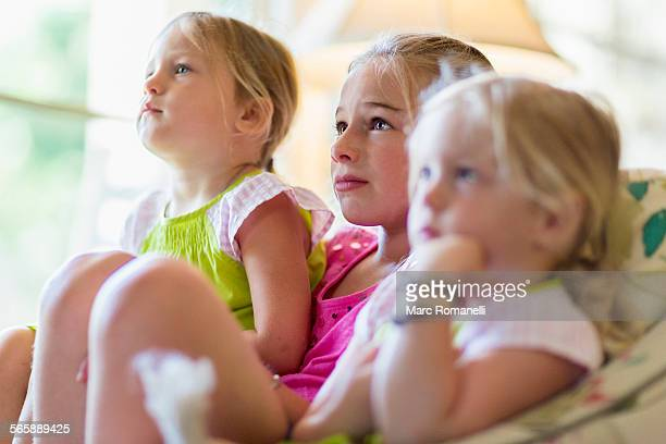 Caucasian girls watching television in armchair