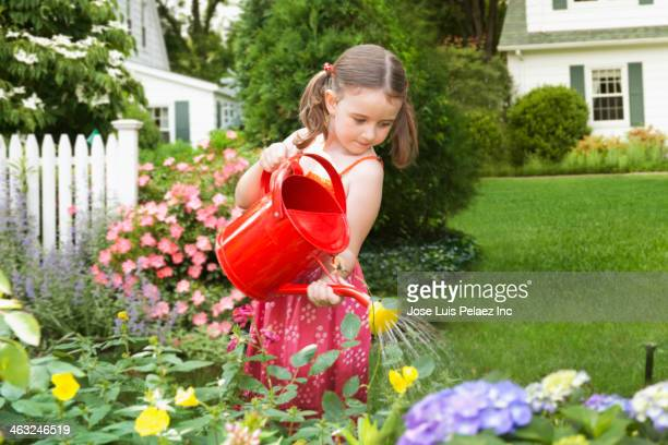 Caucasian girls watering flowers in backyard