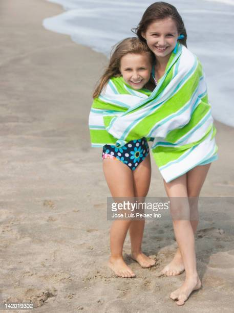 Caucasian girls wrapped together in towel