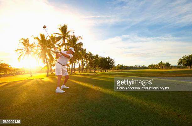 Caucasian golfer hitting ball on golf course