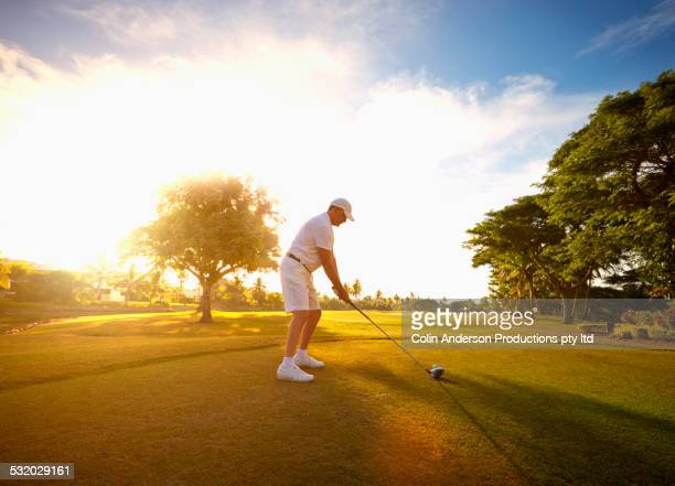 Caucasian golfer holding club at ball on course