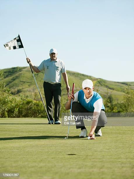 Caucasian golfer placing golf ball on course
