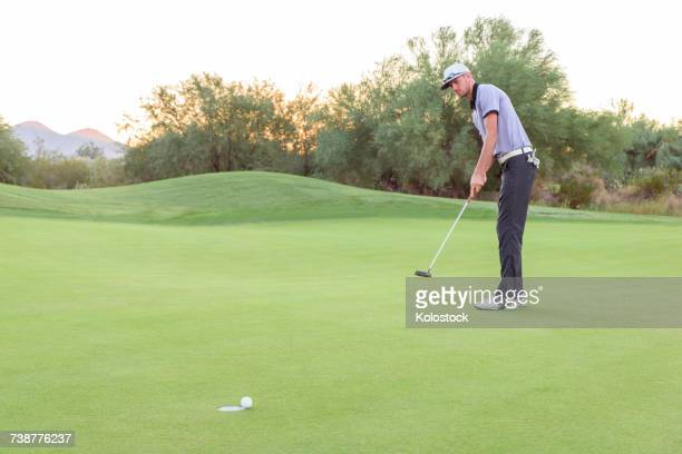 caucasian golfer putting on golf course - putting golf stock pictures, royalty-free photos & images